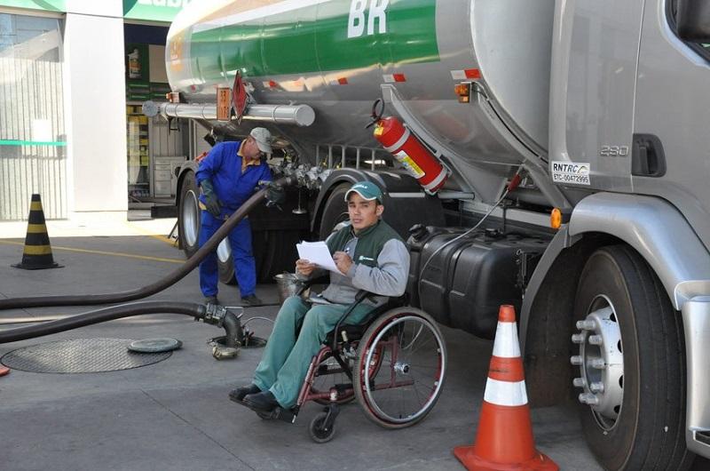 Foto em plano aberto de um posto de gasolina. Há um homem jovem, cadeirante, uniformizado, ao lado de um caminhão-tanque. Ao fundo, um outro funcionorário está com uma mangueira de combustível acoplada ao veículo