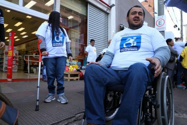 Foto vista de baixo de um homem jovem e cadeirante. Ele usa uma camiseta branca com o logotipo da campanha, uma placa azul, o ícone de cadeirante é destacado, com uma chamada em texto. Ao fundo, há uma mulher muletante, também vestindo a camiseta