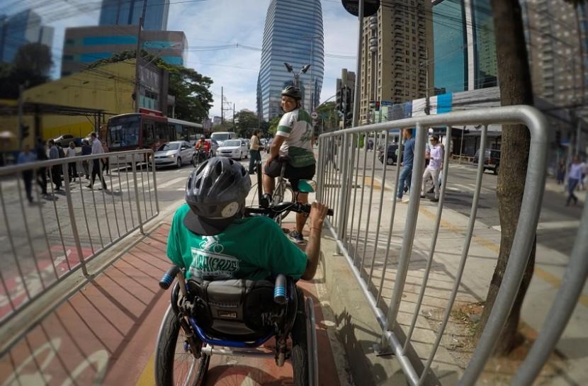 Foto subjetiva de um cadeirante em uma bicicleta adaptada, pedalando em uma ciclovia