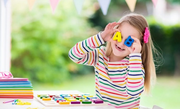 Foto de uma menina de oito anos segurando letras coloridas
