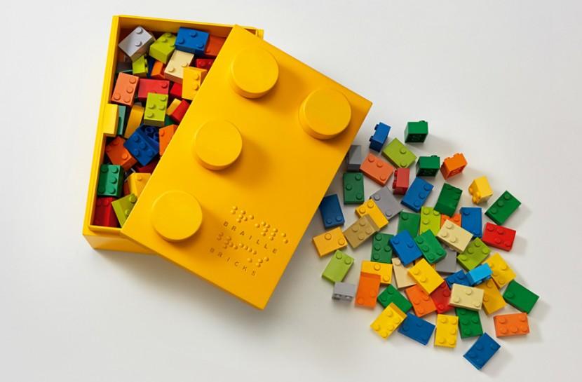 Foto de uma caixa amarela no formato de Lego com peças coloridas dentro e ao redor