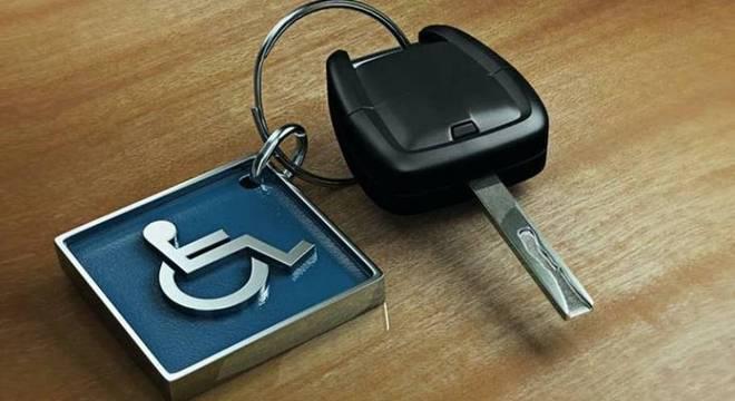 Foto de uma chave de carro presa a um chaveiro de metal quadrado; ele é azul e tem o símbolo de pessoa com deficiência