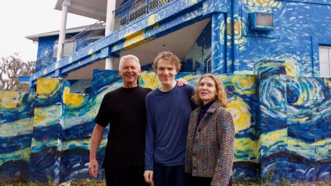 """Foto de um casal de meia idade com um jovem ao centro. Eles estão abraçados em frente à casa de dois andares, com traços similares à obra """"A Noite Estrelada"""""""