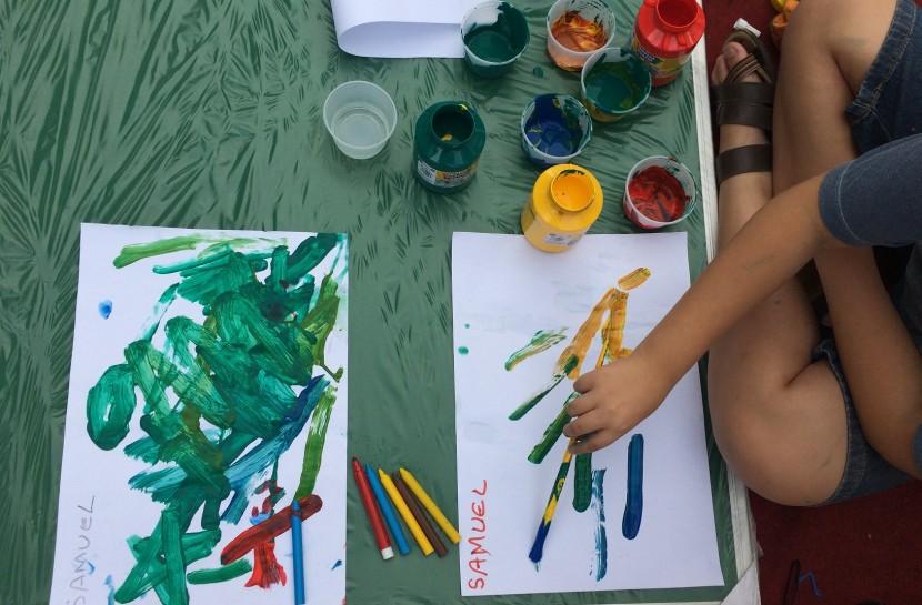 Foto de duas mãos de crianças sujas de tintas coloridas, segurando um pincel e pintando sobre folhas em branco em uma mesa