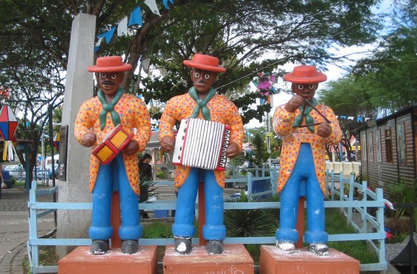 Foto de uma escultura de cerâmica de um Típico trio de forró pé-de-serra: com três homens tocando zabumba, sanfona e triângulo. Eles usam chapéu vermelho, balzer laranja e calça azul e estão em uma praça de Caruaru