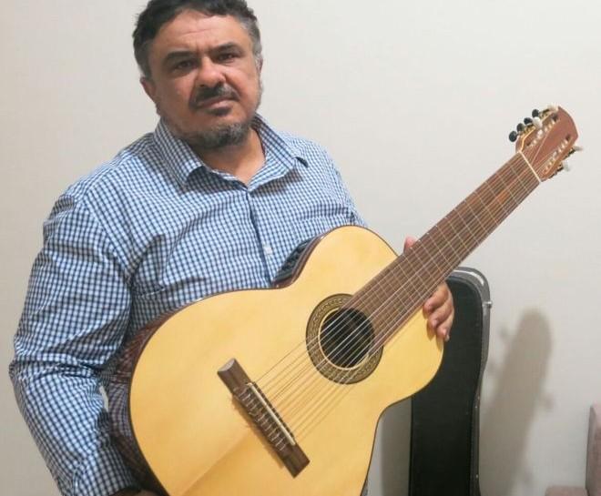 Foto de Reinaldo Amorim Casteluzzo, que segura um violão e olha para a câmera