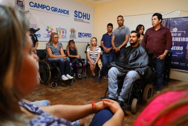 Foto de uma sala fechada, com pessoas de diversas idades reunidas em círculo durante aula de barbearia. Algumas delas estão em cadeiras de rodas
