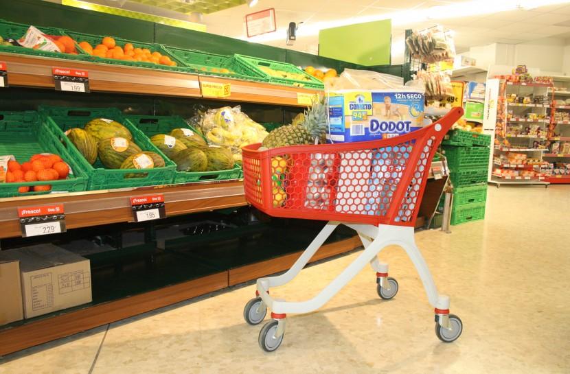 Foto de um carrinho plástico vermelho carregado de compras parado na seção de hortifruti de um supermecado