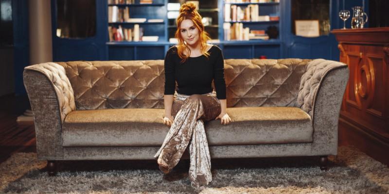 Foto de Luiza Caspary sentada em um sofá em uma sala de estar. Ela é jovem, tem cabelos ruivos, compridos e amarrados em um coque.