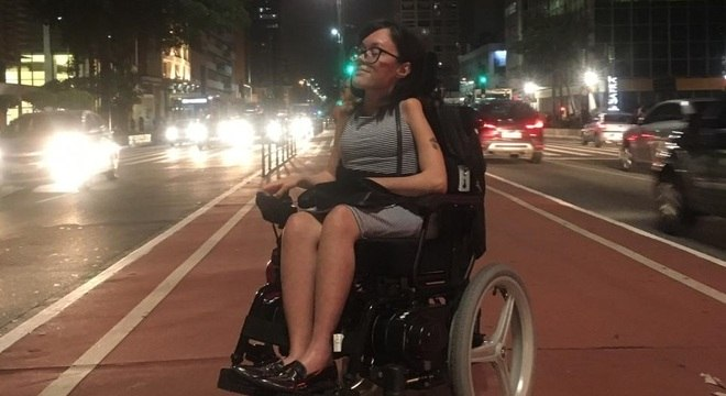 Mulher jovem em cadeira de rodas na Avenida Paulista. Ela é morena, tem cabelos na altura dos ombros e usa um vestido listrado