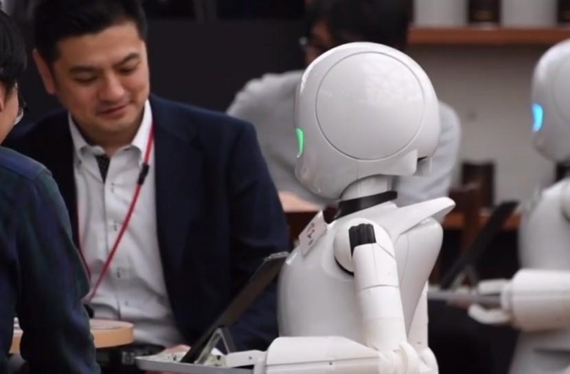 Dois robôs do modelo OriHime-D servindo mesas em um café