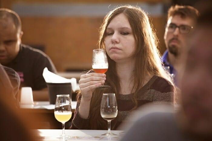 Jovem mulher segurando uma taça de cerveja próxima ao rosto. Ela é branca e tem cabelos na cor castanho claro