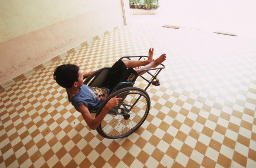 Jovem com deficiência brinca com sua cadeira de rodas em um pátio aberto e iluminado