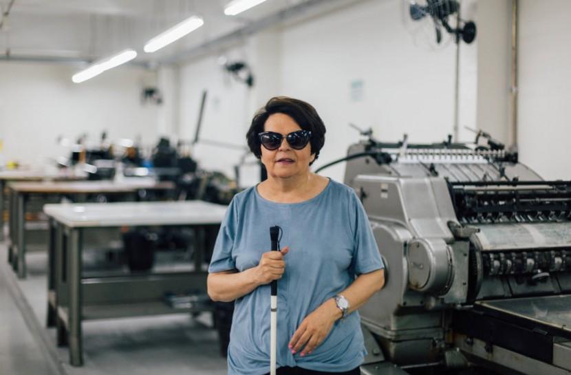 Foto de Regina em pé em frente a máquinas de impressão