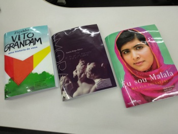 Três livros um ao lado do outro em cima de uma mesa