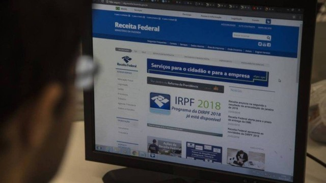 Foto de um homem sentado em uma mesa de escritório navegando no site da Receita Federal