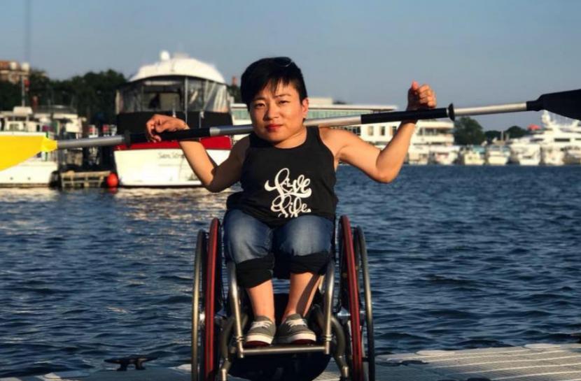 Foto em plano aberto de uma jovem mulher com traços orientais. Ela está em uma cadeira de rodas e segura um remo sobre os ombros