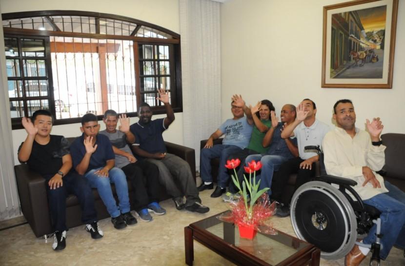 Pessoas com deficiência reunidas na residência inclusiva de Cotia. Estão sorrindo e acenando para a câmera