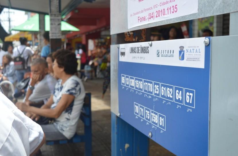 Foto em plano detalhe das placas de ônibus com informações sobre as linhas em numerais e braille