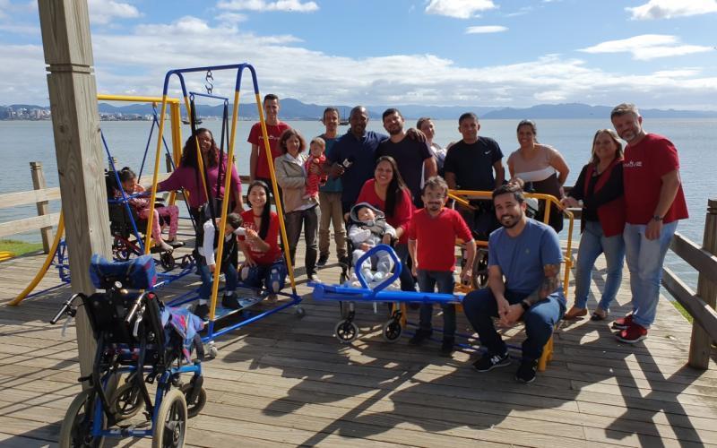 Foto de um grupo de adultos e crianças em um espaço aberto com balanços adaptados para pessoas com mobilidade reduzida