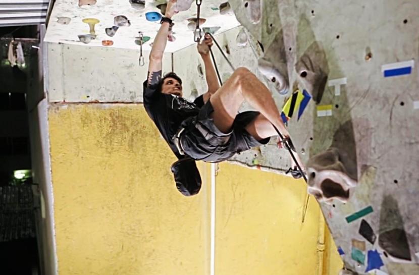 Foto de Daniel, um homem branco de 35 anos, subindo uma parede de escalada