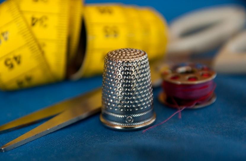 Foto em plano detalhe de um dedal, apoiado em um tecido azul, com uma tesoura, alfinetes e uma fita métrica ao redor