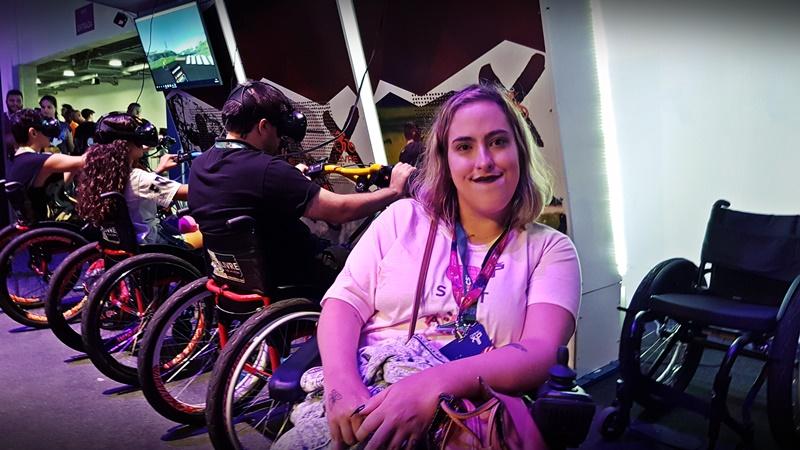 Foto de uma mulher cadeirante na Game XP. Ela olha para a câmera e sorri. Mais atrás, há outros cadeirantes que utilizam óculos de realidade virtual.