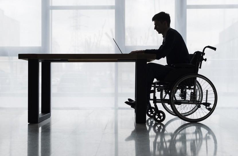 Foto de um homem cadeirante usando um notebook em cima de uma mesa. Ele está sozinho.