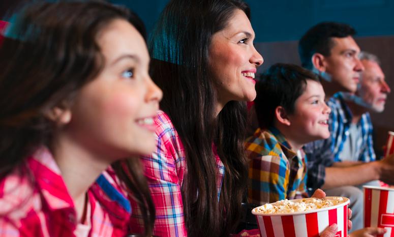 Família assiste a um filme, no cinema