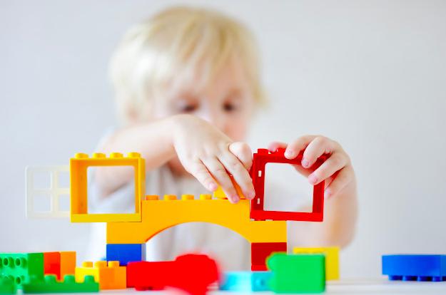 Criança brinca com peças de blocos de encaixar coloridas