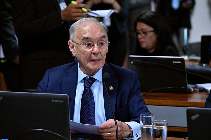 Foto do senador Arolde de Oliveira falando em frente a um microfone no Congresso. Ele é um homem de cabelos brancos, está usando um terno e gravata azuis e uma camisa azul claro.