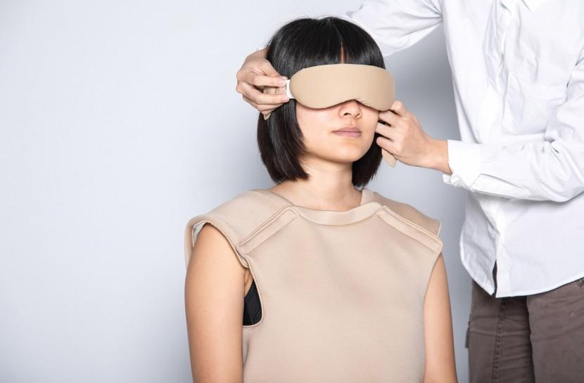 Foto de uma mulher sentada, usando um colete e uma máscara que tapa seus olhos. Ao lado dela, há uma pessoa em pé, que a ajuda a posicionar a máscara.