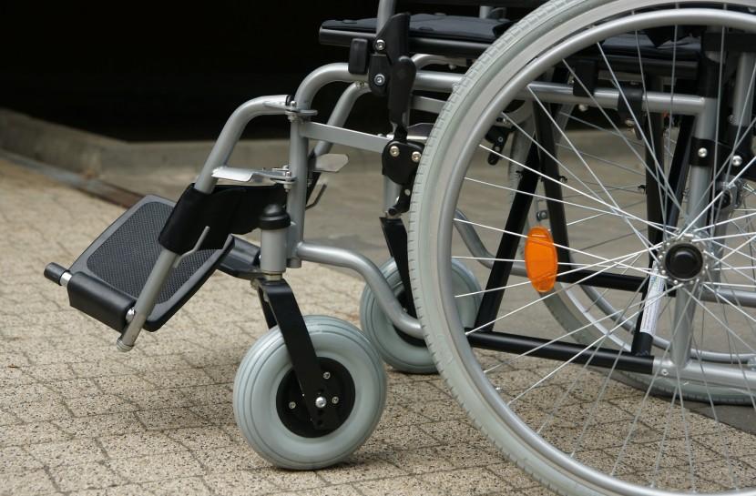 Foto de uma cadeira de rodas parada em cima de uma calçada.